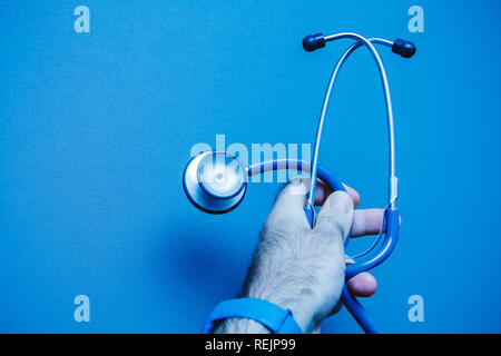 Close-up of a young male doctor's hand holding a stethoscope on blue isolated background. Stethoscopes are very often considered an emblem of healthcare professionals. - Stock Photo