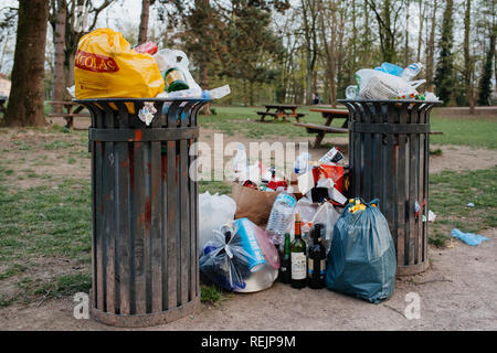 STRASBOURG, FRANCE - APR 7, 2018: Overflowing waste bins full with various types of trash such as bottles, pizza boxes and plastic bags near a picnic designated area equipped with wooden tables and benches in a French city park on a spring day.  - Stock Photo