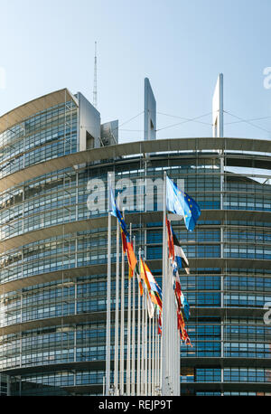 Facade of the European Parliament building in Strasbourg, France with all European Union Member States flags waving in the courtyard of the Louise Weiss building on a fine sunny spring day - Stock Photo