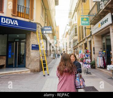 FELANITX, PALMA DE MALLORCA, SPAIN - MAY 10, 2018: Ladder next insignia logotype of the Spanish BBVA bank during installing fiber optic internet cable above entrance - Stock Photo