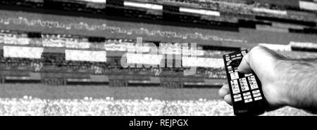 Man with large tv remote trying to fix the digital television noise on a large plasma OLED 4K Ultra HD High Dynamic Range HDR Smart TV - black and white. - Stock Photo