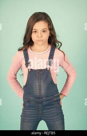 Kid fashion, casual style. Little girl pose in jeans overall, fashion. Child with long brunette hair, beauty. Beauty, look, hairstyle. Childhood, youth punchy pastel trend - Stock Photo