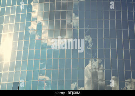 Clouds reflected on glass facade wall of building. Cloudy blue sky reflection in windows. Modern glass architecture. Architecture background. structure and design. Future and development. - Stock Photo