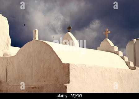 Church dome and crosses in Mykonos, Greece. Chapel building detail architecture. White church on cloudy blue sky. Religion and cult concept. Summer vacation on mediterranean island. - Stock Photo