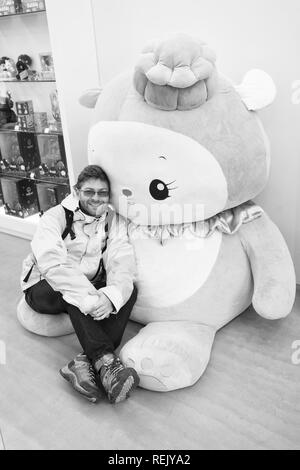 Reykjavik, Iceland - October 12, 2017: man traveler with hello kitty toy. Leisure traveler man. Hello, handsome. Hello Kitty is a cartoon character produced by the Japanese company. - Stock Photo