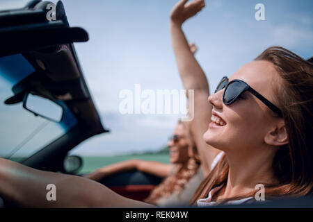 close up.two young women traveling in a car - Stock Photo