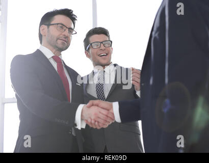 business partners shaking hands at the beginning of the meeting - Stock Photo