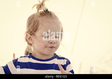 Baby boy with blond hair ponytail in sailor shirt on sunny summer day outdoors. Nautical fashion, vacation style concept. - Stock Photo