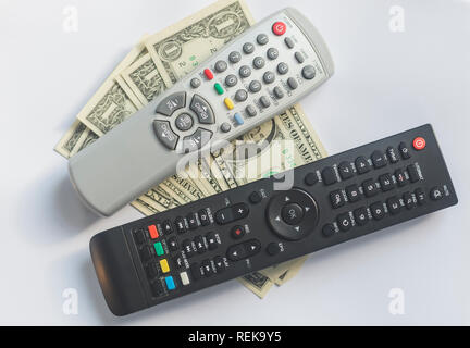 TV Remotes and US dollars on white background. Pay TV or television concept. - Stock Photo