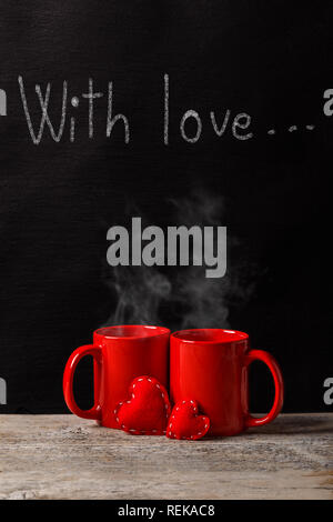 With love phrase handwritten with white chalk on blackboard and two cups of tea on wooden board - Stock Photo
