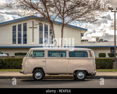 A vintage VW bus parked on the street in front of church. - Stock Photo