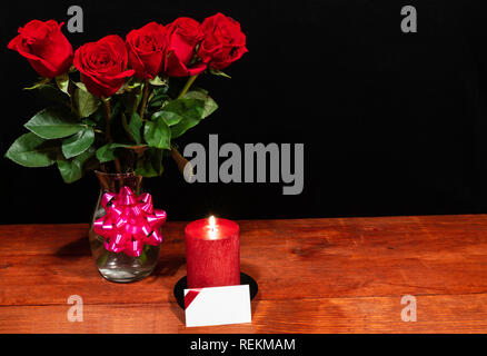 Beautiful red roses in vase with pink bow and red candle with name tag on wooden table on dark background. Valentines, Mothers Day, Easter, Christmas, - Stock Photo