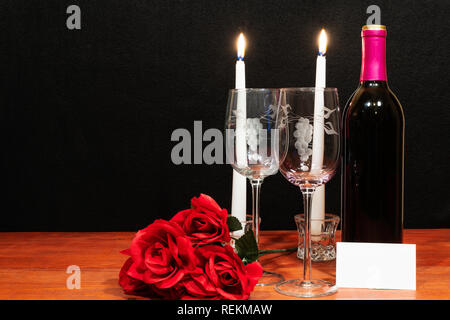 Beautiful etched wine glasses and bottle of red wine, white candles and red roses on wooden table with name tag on dark background. Valentines, Mother - Stock Photo