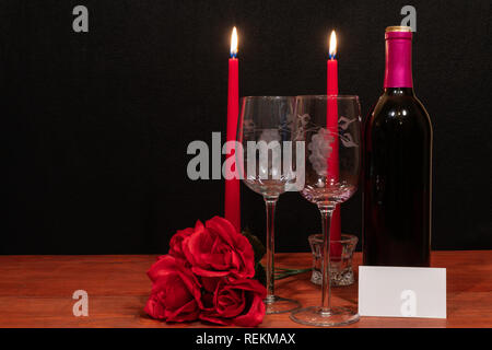 Beautiful etched wine glasses and bottle of red wine, red candles and red roses on wooden table with name tag on dark background. Valentines, Mothers  - Stock Photo