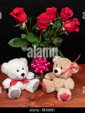 Two cute cuddly teddy bears with red roses in vase and pink bow on wooden table on dark background. Valentines, Mothers Day, Easter, Christmas, Weddin - Stock Photo