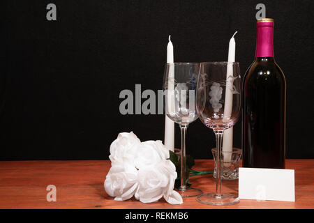Beautiful etched wine glasses and bottle of red wine, white candles and white roses on wooden table with name tag on dark background. Valentines, Moth - Stock Photo