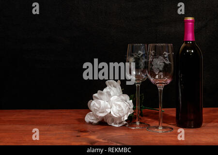 Beautiful etched wine glasses and bottle of red wine and white roses on wooden table and dark background. Valentines, Mothers Day, Easter, Christmas,  - Stock Photo