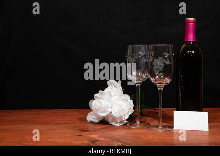 Beautiful etched wine glasses and bottle of red wine and white roses on wooden table with name tag on dark background. Valentines, Mothers Day, Easter - Stock Photo