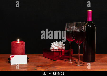 Beautiful etched wine glasses and bottle of red wine, red candle, wrapped present with bow on wooden table with name tag on dark background. Valentine - Stock Photo