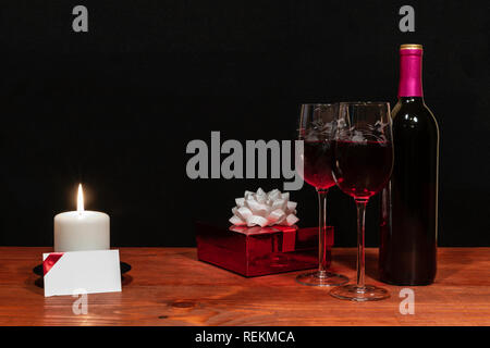 Beautiful etched wine glasses and bottle of red wine, white candle, wrapped present with bow on wooden table with name tag on dark background. Valenti - Stock Photo