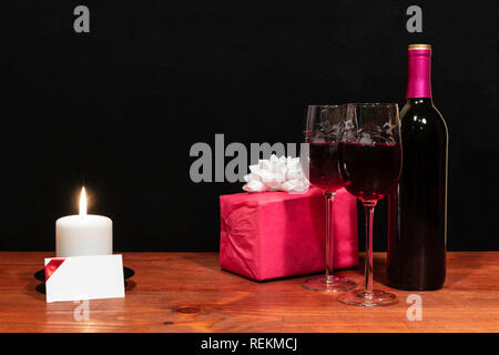 Beautiful etched wine glasses and bottle of red wine, white candle, wrapped present with bow on wooden table with name tag on dark background. - Stock Photo