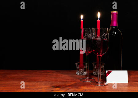 Beautiful etched wine glasses and bottle of red wine, red candles, on wooden table with name tag on dark background. Valentines, Mothers Day, Easter,  - Stock Photo