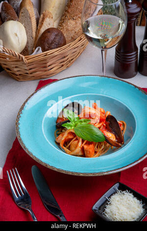 Italian cuisine. Pasta with seafood, tomatoes and cheese in a blue, a fork and a knife on a light background. - Stock Photo