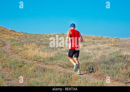 rear view of athletic runner running on a mountain trail on a blue sky background - Stock Photo