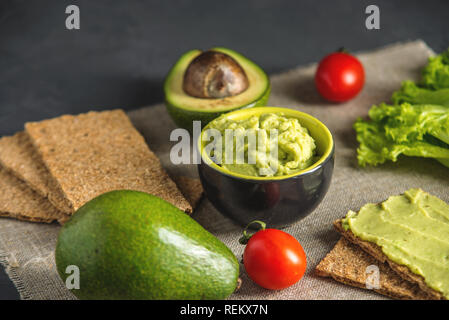 Traditional Mexican cold appetizer made of pureed avocado pulp with bread and vegetables on the table. Concept healthy vegetarian Breakfast - Stock Photo