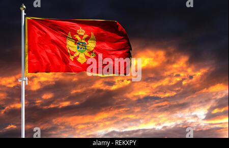 flag of Montenegro on flagpole fluttering in the wind against a colorful sunset sky. - Stock Photo