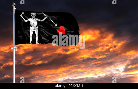 flag of Blackbeard Pirate on flagpole fluttering in the wind against a colorful sunset sky. - Stock Photo