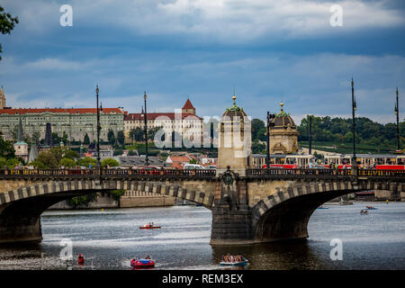 PRAGUE, CZECH REPUBLIC - AUGUST 28, 2015: Pedal boats sail and pass under the medieval stone Chec Bridge on Vltava River, Prague, Czech Republic - Stock Photo