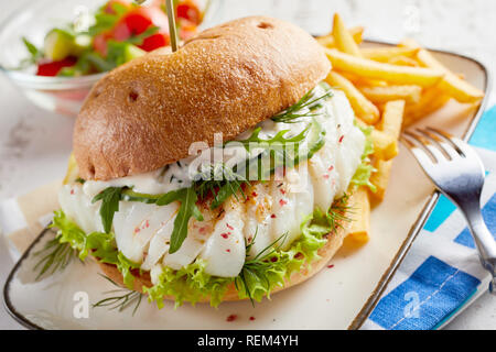 Gourmet fish seafood burger with mayo and fresh salad greens and herbs on a crusty bun with side serving of potato chips - Stock Photo