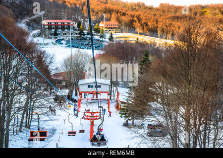 People on the lift enjoy the stunning view of the famous greek ski center 3-5 Pigadia. - Stock Photo