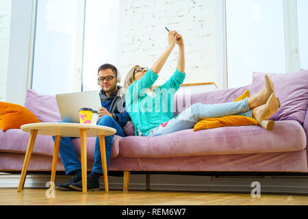 Man and woman sit on the couch, chatting and using smartphone, desktop computer. - Stock Photo