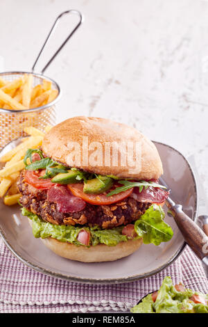 Pork belly burger with fresh avocado and crispy fried bacon, rocket, tomato ad lettuce on a crusty bun served with potato chips with copy space - Stock Photo