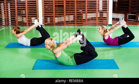 Girls practicing yoga, Yoga Dhanurasana / Bow pose - Stock Photo