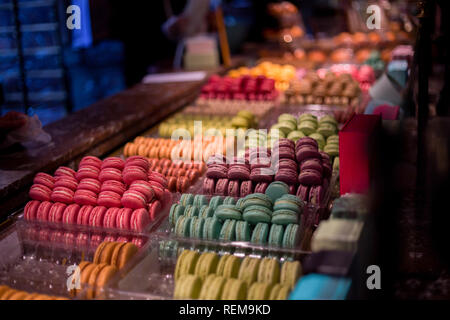 A stand with different flavors of macarons inside a shop in Paris. - Stock Photo