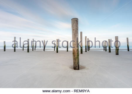Poles on a beach with blue sky long exposure landscape - Stock Photo