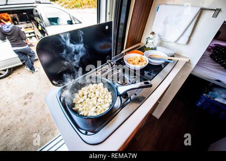 Cooking dinner or lunch in campervan, motorhome or RV. Preparing chicken  in a pan in camper van when traveling with RV, motor home caravan or motorva - Stock Photo