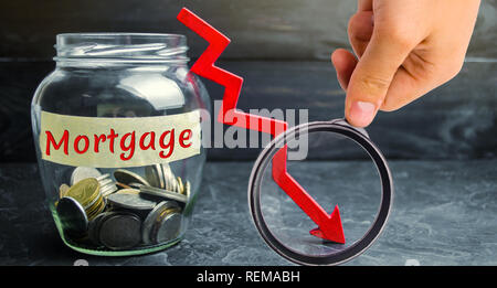 Glass jar with coins and the inscription 'Mortgage' and down arrow. Reduced interest in the mortgage. Low interest rates. Falling real estate prices. - Stock Photo