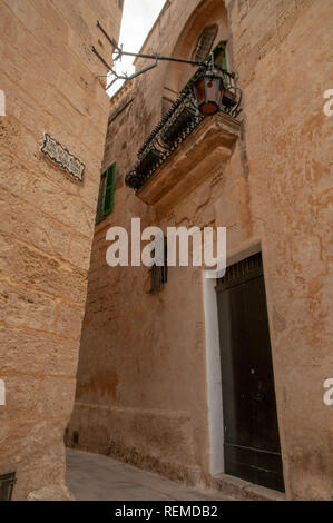 A typical narrow street between limestone houses in the ancient, walled city of Mdina in Malta. - Stock Photo