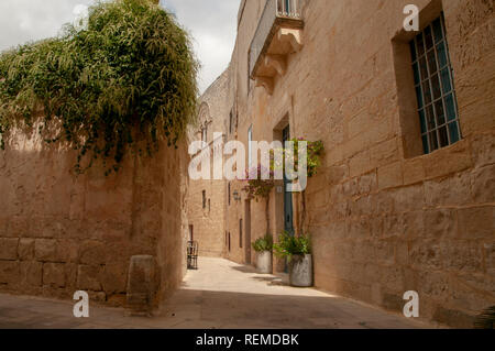 Typical narrow streets between limestone houses in the ancient, walled city of Mdina in Malta. Here on the corner of Gatto Murina Street and Mesquita  - Stock Photo