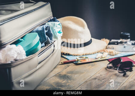 Open suitcase with female clothes for trip vacation. Packing things. - Stock Photo