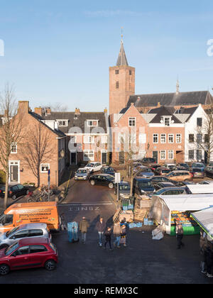naarden, netherlands, 19 january 2019: people on open air market in the foreground of large old curch in dutch town of naarden vesting - Stock Photo