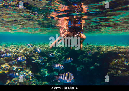 Young woman snorkeling making okay signs underwater near coral reef - Stock Photo