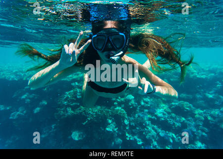 Young woman snorkeling making peace signs underwater - Stock Photo