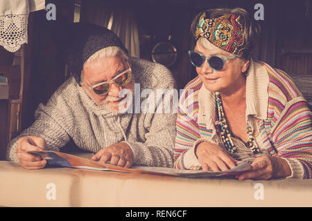 Adults mature couple of caucasian people hippy style planning on the map the next step of van life vacation - cheerful happy man and woman retired and - Stock Photo