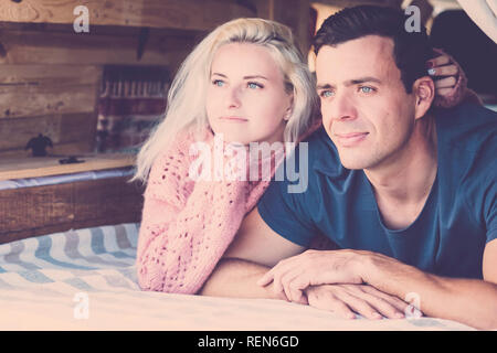Young beautiful millennial couple looking outside laying down in a little vintage nice camper van during alternative vacation enjoying nature and trav - Stock Photo