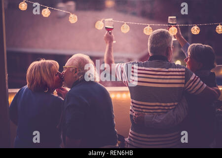 Romantic and love concept with two senior adults couple celebrate together at home in a terrace with city view - toasting with wine and kissing - matu - Stock Photo